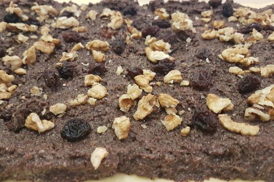 Rozwałkowana warstwa ciasta drożdżowego z masą makową posypana rodzynkami, żurawiną i orzechami włoskimi.