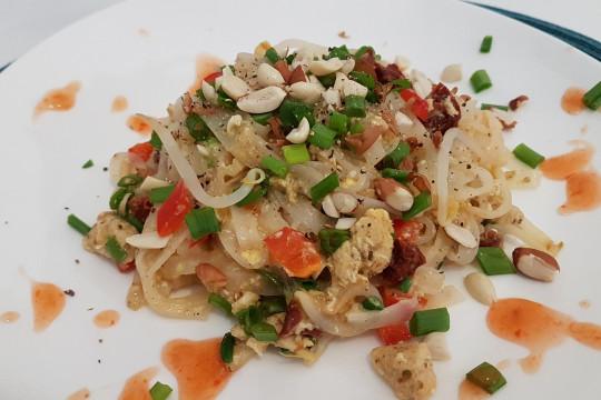 Makaron z warzywami i kurczakiem posypany szczypiorkiem i orzechami. Oprószony świeżo zmielonym pierzem, skropiony limonką i sosem.