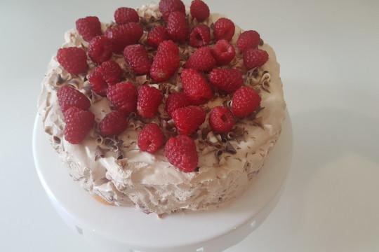Ciasto udekorowane malinami i czekoladą.