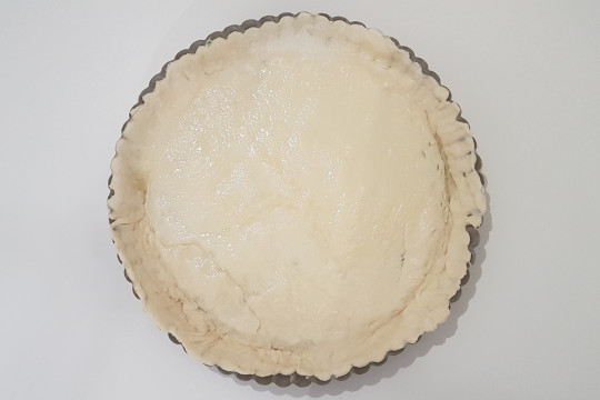 Okrągła forma wylepiona ciastem.
